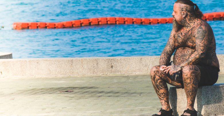Hombre tatuado en la piscina.
